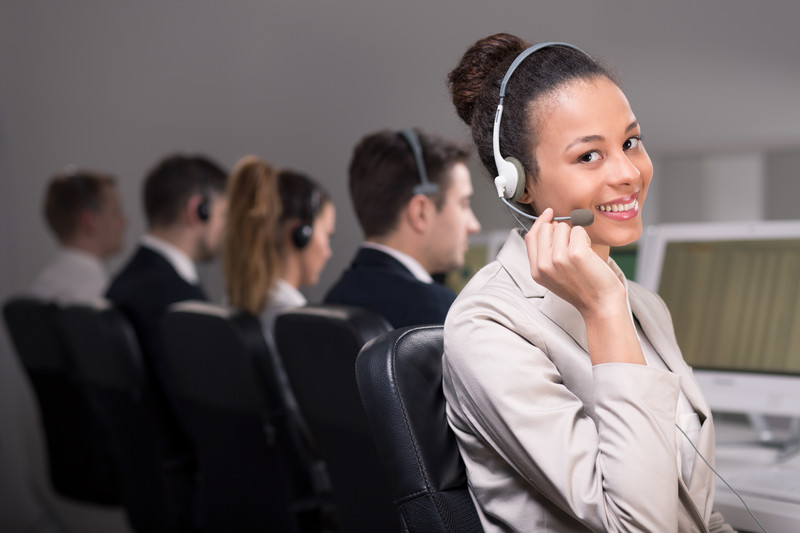 This photo shows a smiling woman in light-colored business clothing and a headset looking at the camera at the end of a row of similarly-dressed people who are looking at computer screens in front of them, representing the best call center affiliate programs.