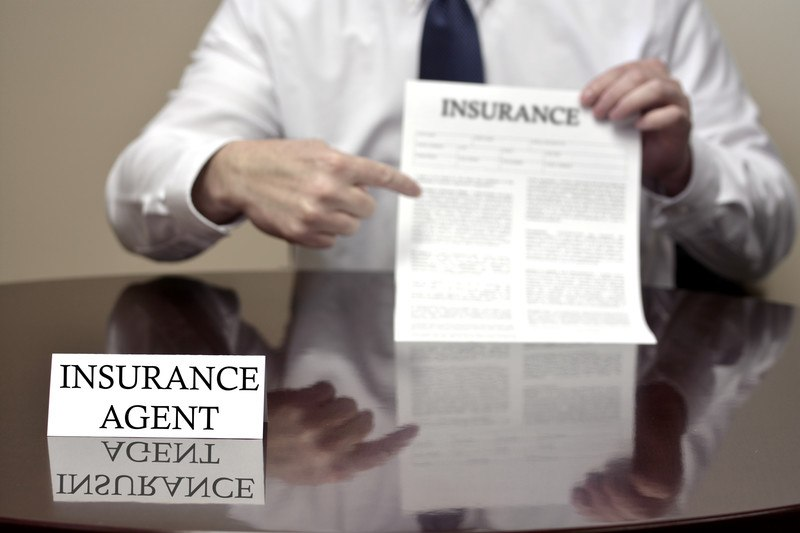 This photo shows the shoulders and arms of a businessman in a white suit and dark tie holding a white paper with black text and the word 'Insurance' at the top above a polished wooden desk with an insurance placard on top of it, leading readers to ask: do insurance agents make good money?