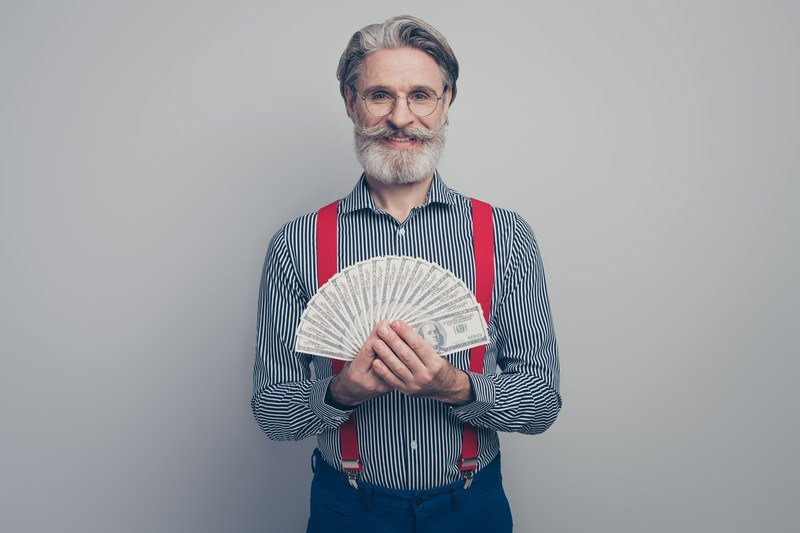This photo shows a smiling white-bearded man in a striped shirt, blue pants, and red suspenders holding several $100 bills in a fan shape in front of him, representing the best lifetime commissions affiliate programs.