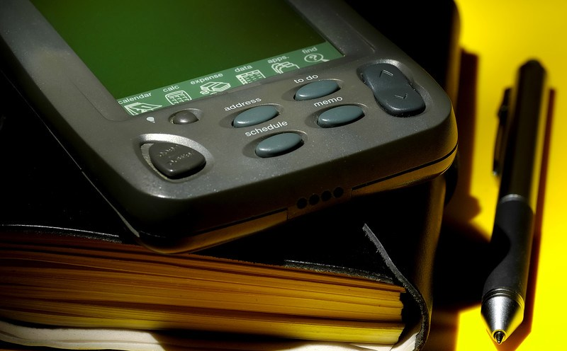 This photo shows a mobile device lying on a black organizer on a yellow table, beside a black pen, representing the best organizer affiliate programs.