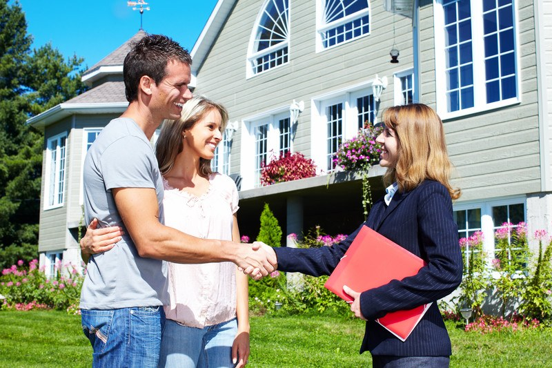 This photo shows a smiling woman real estate agent in a dark blue jacket, holding a red folder, shaking hands with a smiling couple on the lawn in front of a large gray and white house.