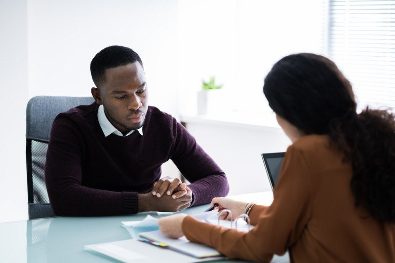 This photo shows a dark-skinned, dark-haired man and woman in business clothing discussing financial documents across a blue table, representing the best tax preparers in action.
