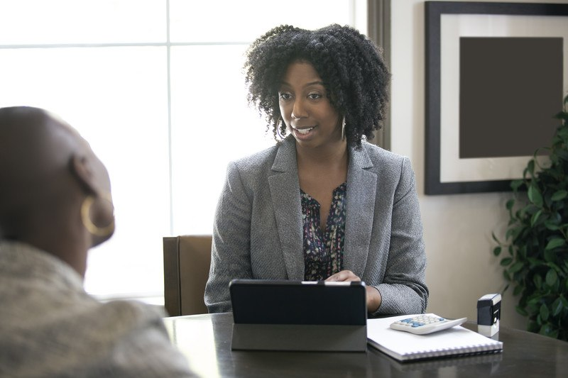 This photo shows a dark, curly-haired woman in a gray business jacket sitting in front of a window, with a computer in front of her, talking with another woman about finances, representing the best tax preparers