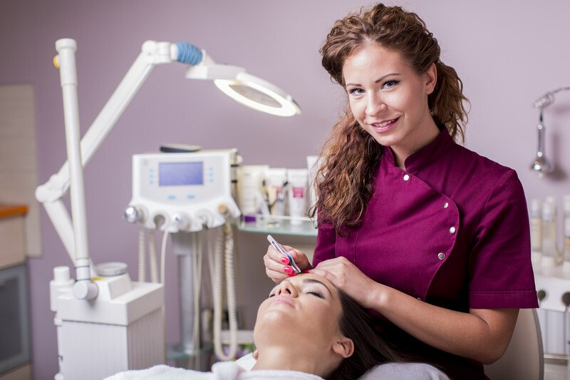 This photo shows a smiling brunette esthetician in a burgundy lab coat doing a cosmetic procedure on a woman lying on the table in front of her, representing an answer to the question: Do estheticians make good money?