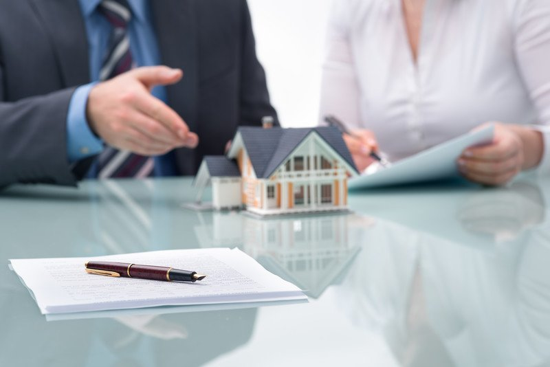 This photo shows the shoulders of a man in a business suit, blue shirt and striped tie next to a woman in a white shirt who is writing something on a piece of paper while the ma gestures toward a model of a pink and white house near a stack of paperwork and a pen lying on a shiny table in front of them.