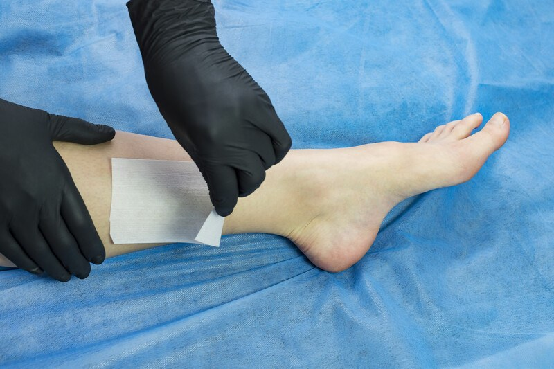 This photo shows a pair of hands in black gloves peeling wax from a woman's legs, on top of a blue blanket.