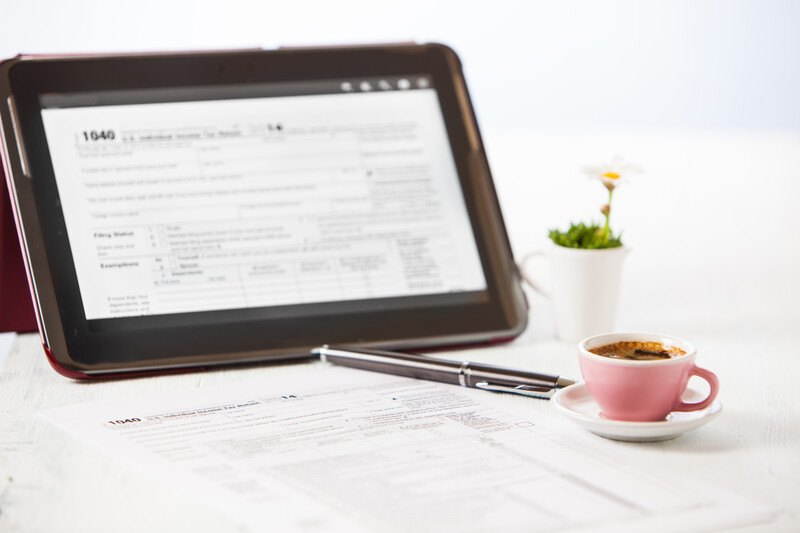 This photo shows a tax document 1040 loaded on the screen of a small computer, along with a potted plant, a pen, printed tax forms, and a pink coffee cup with coffee in it on a white saucer.