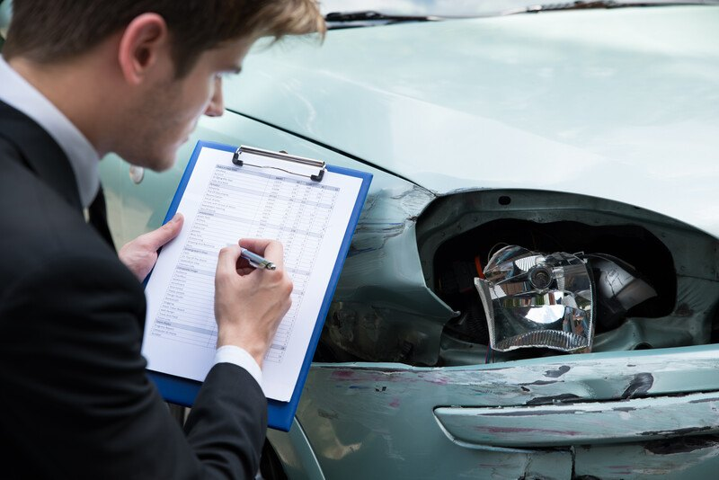 This photo shows a brown-haired male insurance agent writing something a clipboard as he looks at damage done to a light-colored car near one of the headlights.