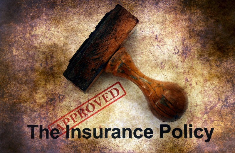 This photo shows a wooden stamp and a red stamp of approval on an insurance policy on a grown and white background.