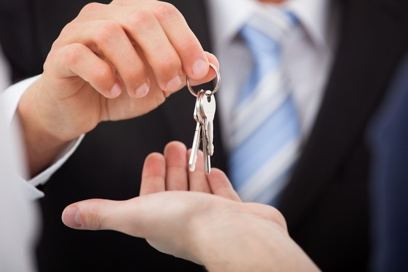 This photo shows a the hand of a man in a dark business suit and white and blue tie dangling a set of keys over a woman's outstretched hand.