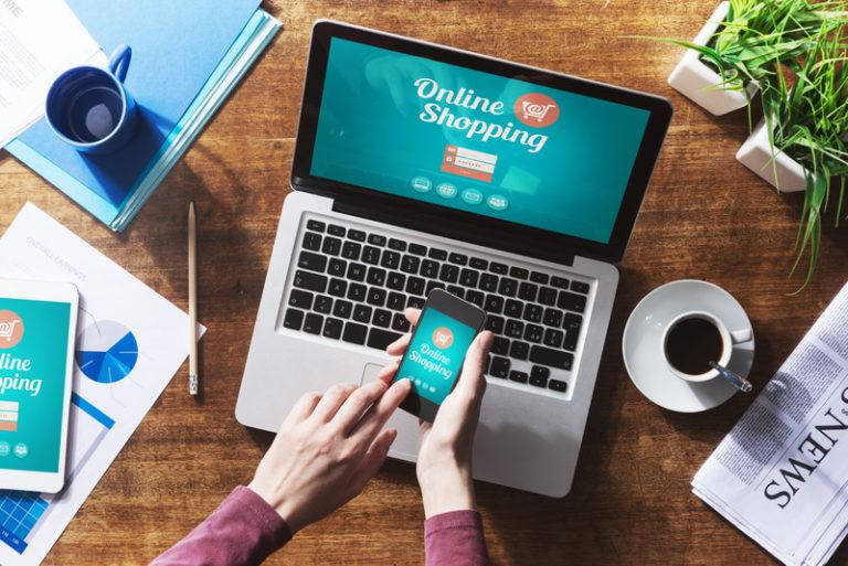 This overhead photo shows a woman's hands holding a mobile phone above a laptop, both of which have an online shopping screen loaded, along with papers, coffee cups, and potted plants on wooden desk, representing the best online retail affiliate programs.