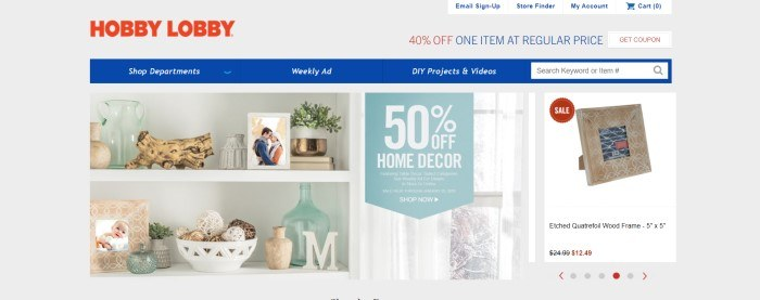 This screenshot of the home page for Hobby Lobby has a gray background, red logo, blue navigation bar, and a main section with a photo showing white shelves full of knick-knacks, along with white text announcing 50% off home décor.