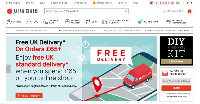 This screenshot of the home page for Japan Centre has a white background with black text and navigation bar above a graphic of a red bus driving on a gray map with red text announcing free delivery, with a blue text section on the left with black and red text and a red call to action button and an advertising column on the right.