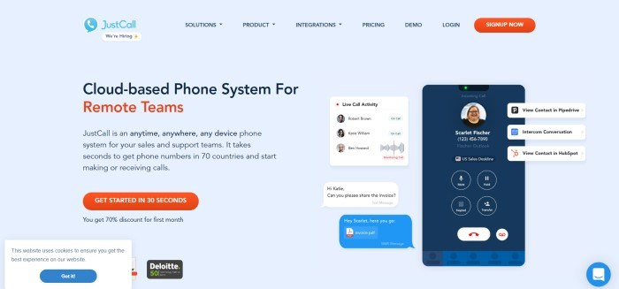 This screenshot of the home page for JustCall has a pale blue background with a transparent navigation bar, an orange call to action button, text in black and red on the left side of the page, along with another orange call to action button, and inserts of screen activity on the mobile device on the right side of the page.