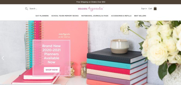 This screenshot of the home page for MomAgenda has a dark header, a white navigation bar with a pink logo, and a photo showing a variety of different day planners and organizer books in pink, aqua, black, purple, and beige on a whte table next to a beige candle jar with a lit candle and a vase of white flowers.