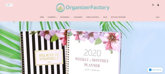 This screenshot of the home page for Organizer Factory has a pink navigation bar above a photo of a black and white striped journal with a floral design and a 2020 planner with a white background and floral design against a white background with green leaves.