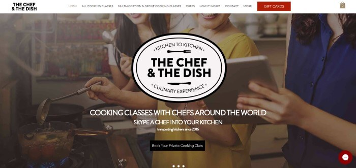 This screenshot of the home page for The Chef And The Dish has a white navigation bar with a red tab for gift cards above a photo of three smiling women looking at a tablet while cooking, along with white and black text inviting people to try at-home cooking classes, and a black call to action button.