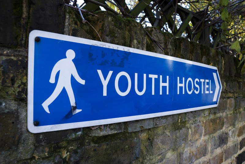 This photo shows a blue sign with white text reading 'youth hostel' and a white icon of a person walking, hanging on a brick wall under green branches, representing the best hostel affiliate programs.