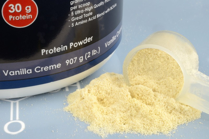 This photo shows a transparent scoop of white protein powder, with the powder spilling out of it, next to a black-labeled jar of protein powder on a light blue surface, representing the best protein powder affiliate programs.