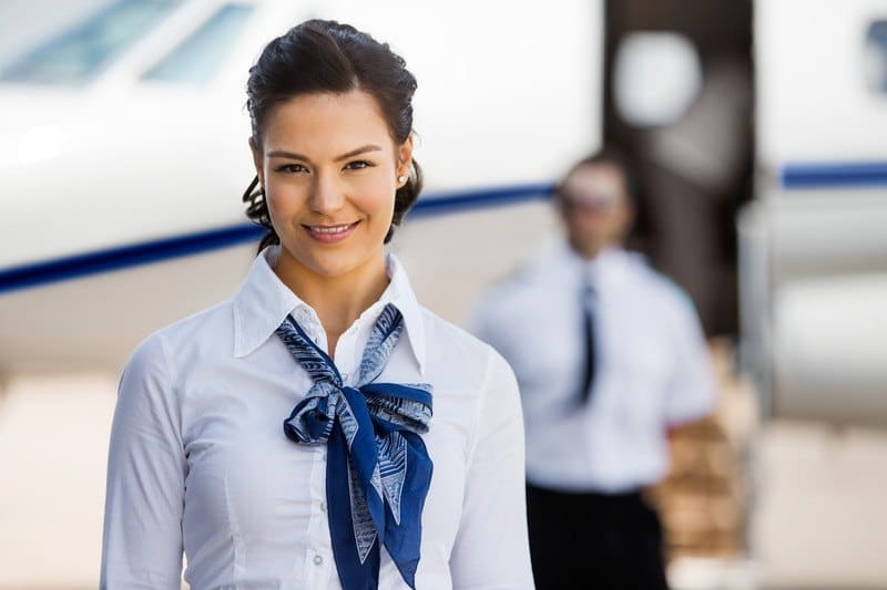 This photo shows a smiling dark-haired woman in a white shirt and blue tie, standing in front of an airplane with an open door and a man in a white shirt and blue tie at the bottom of the airplane stairs, representing the question: do flight attendants make good money?