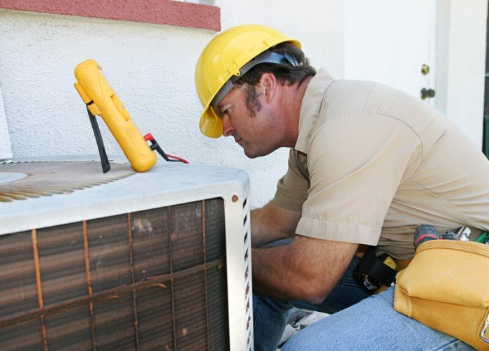 This photo shows a man in a tan shirt, yellow hard hat, and jeans working on an air conditioning unit outside a white stucco building, representing the question: Do HVAC technicians make good money?