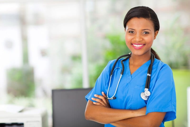 This photo shows a smiling dark-haired woman in blue scrubs standing with her arms folded in front of a window, representing the question, do nurses make good money?