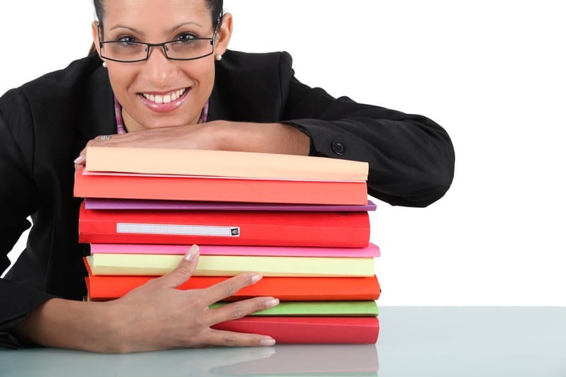 This photo shows a smiling woman in glasses and a dark business jacket leaning across a stack of legal document binders in shades of red and orange, representing the question, do paralegals make good money?