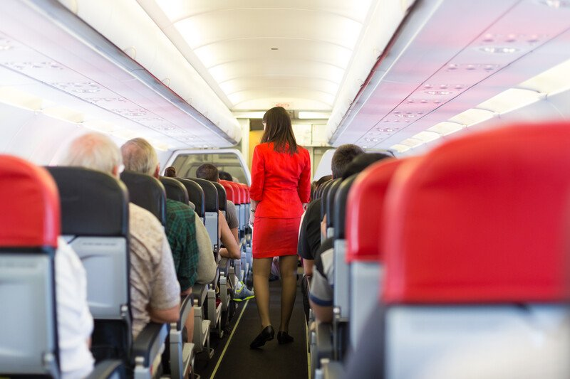 This photo shows a dark-haired woman in a red flight attendant suit walking down the aisle of a crowded airplane cabin.