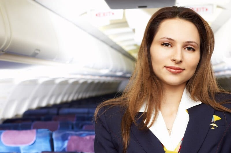 This photo shows a brunette woman in a white shirt, blue jacket, and yellow airline pin standing in the empty cabin of an airplane.