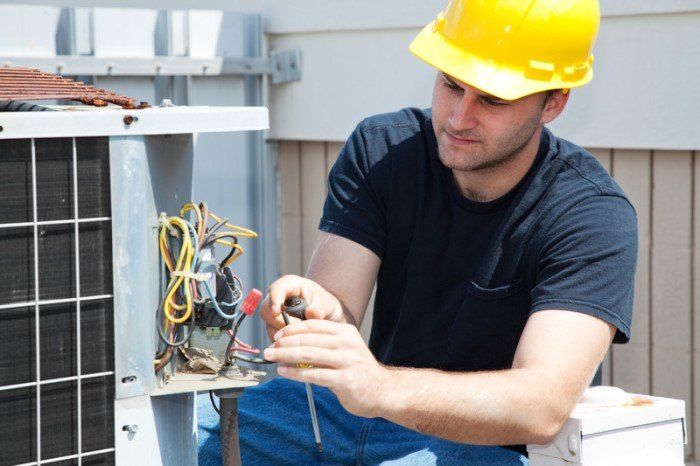 This photo shows a young man in a yellow hard hat, black tee shirt, and jeans working on a the wiring section of an air conditioning unit outside a brown and white building, depicting an HVAC technician at work.