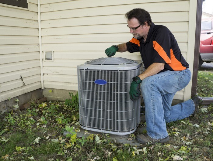 This photo shows a repairman in jeans and an orange and black shirt fixing an air conditioning unit outside a cream-colored home.