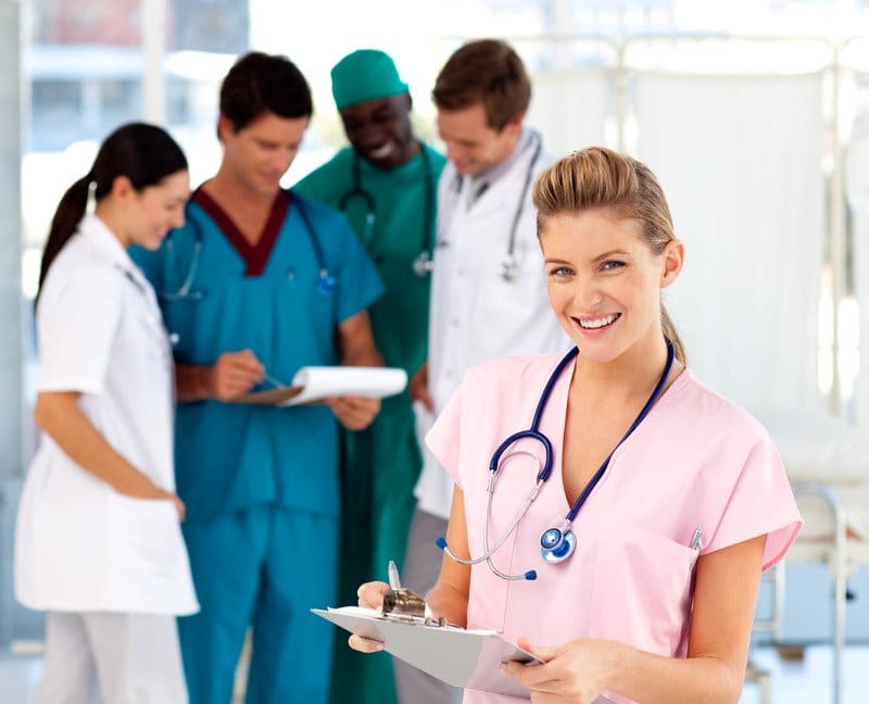 This photo shows a smiling blonde woman in pink scrubs, holding a clipboard, standing in front of a group of doctors and nurses in white, blue, and green clothing, in a hospital setting, representing the idea that nurses have good job satisfaction.
