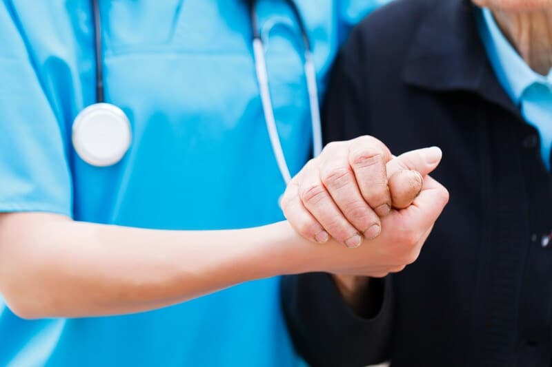This photo shows a neck-to-waist shot of a woman in a blue nursing uniform holding the hand of an elderly woman in a dark jacket, representing a nurse at work.