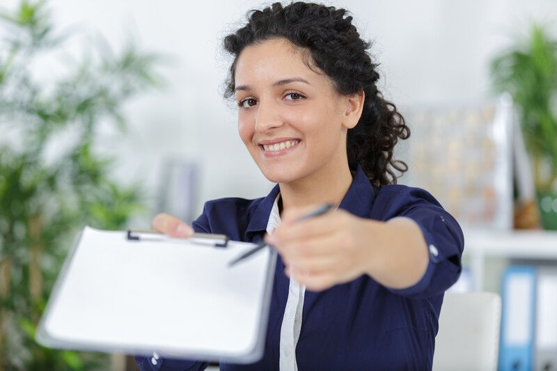 This photo shows a smiling dark-haired woman in white and navy blue business clothing holding out a clipboard and pen.