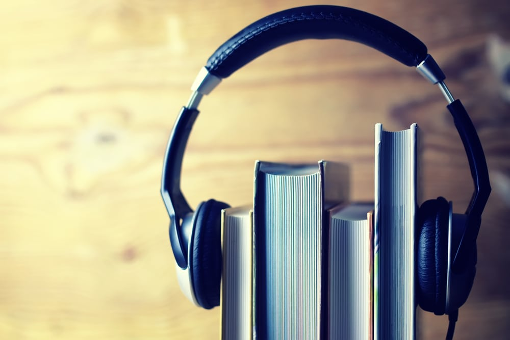 large headphones around stack of books