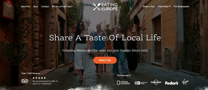 This screenshot of the home page for Eating Europe has a transparent navigation bar with white text overlaying a large photo of a group of travelers walking down a narrow European street behind white text and an orange call to action button.