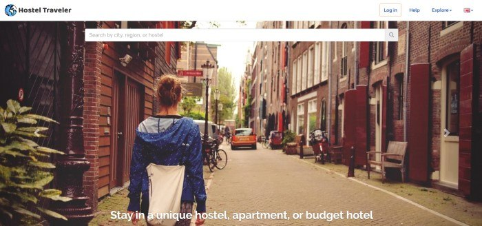 This screenshot of the home page for Hostel Traveler has a white header and search bar overlaying a photo showing the back of a woman in a blue jacket walking down a narrow European street.