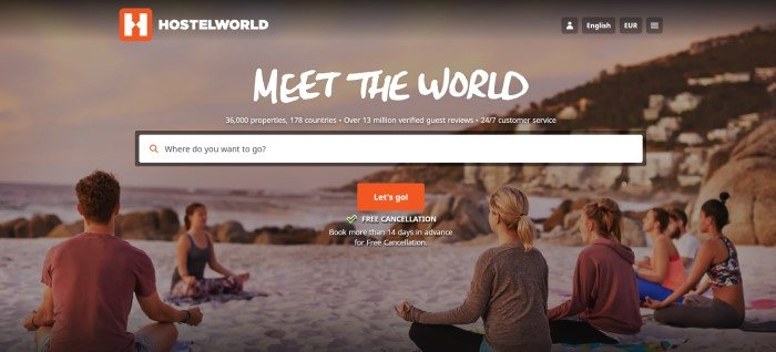This screenshot of the home page for Hostelworld has white text, a red and white logo, a white search bar, and a red call to action button overlaying a photo of several millennials meditating in a yoga sitting position on a beach.