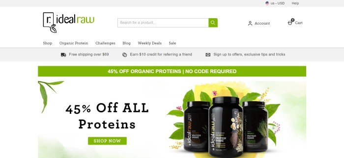 This screenshot of the home page for Ideal Raw has a white search bar and navigation bar with a black and green logo above a gray announcement gar, a green announcement bar, and a white main section with black text and a green call to action button on the left side of the page and a photo of three black canisters of protein powder, along with a yellow background, pink flowers, and green leaves, on the right side of the page.