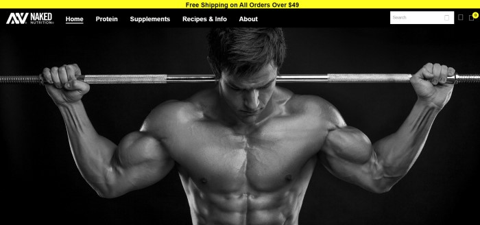 This screenshot of the home page for Naked Nutrition has a yellow announcement bar above a transparent navigation bar with white lettering and a search window, which is overlaying a black background with a black and white photo of a muscular man looking down as he holds a metal bar across his shoulders.