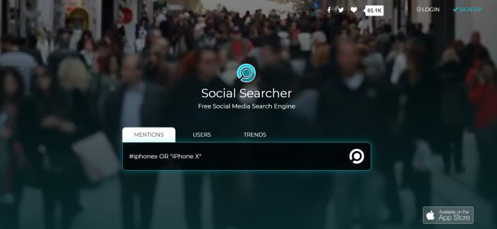 This screenshot of the home page for Social Searcher has a dark filtered, blurred screenshot of a people-crowded street, behind an aqua logo, white text, and a black search bar.