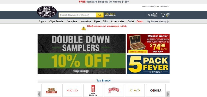 This screenshot of the home page for Thompson Cigar has a gray and white header, search bar, and navigation bar above a white main section with a green, black, yellow and gray sales section on the left and a red, black, and yellow sales announcement on the right, above a row showing the icons of the top brands of cigars carried by this company.