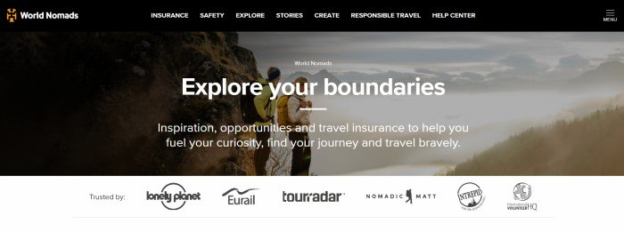 This screenshot of the home page for World Nomads has a black navigation bar with white text above a large photo showing two young travelers in coats and backpacks looking out over a misty valley, behind white text and above a white section with black logos of partner companies.