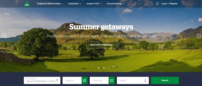 This screenshot of the home page for YHA has a dark blue header with white text above a photo of a green countryside, along with more white text and a transparent call to action button with a white outline and white text, as well as a dark gray search bar at the bottom of the page.