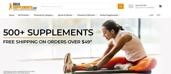 This screenshot of the home page for Bulksupplements.com has a search bar and navigation bar with an orange and black logo above a main section with a large photo showing a smiling dark-haired woman in peach and orange exercise clothing stretching her legs, behind black text announcing free shipping and more than 500 supplements.