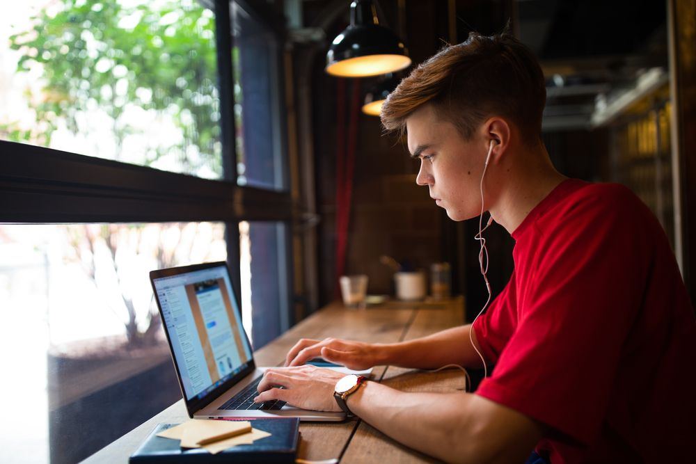 young man at cafe doing online virtual assistant work