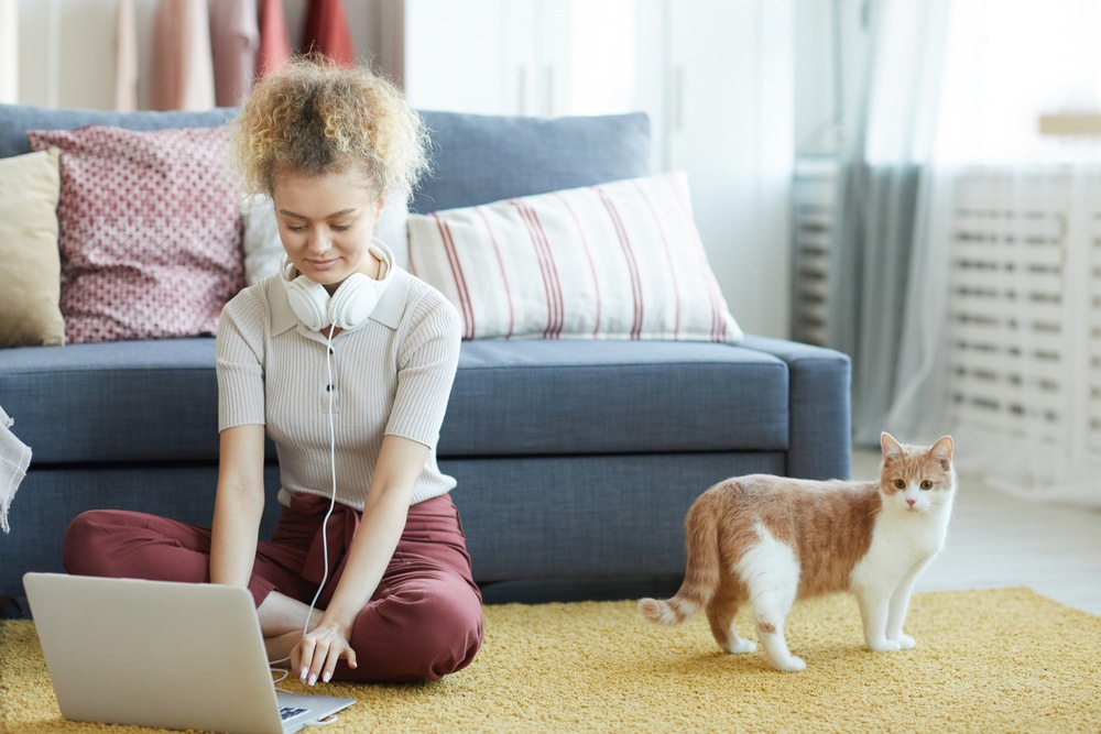 young woman sitting on the floor doing online transcription work with her cat