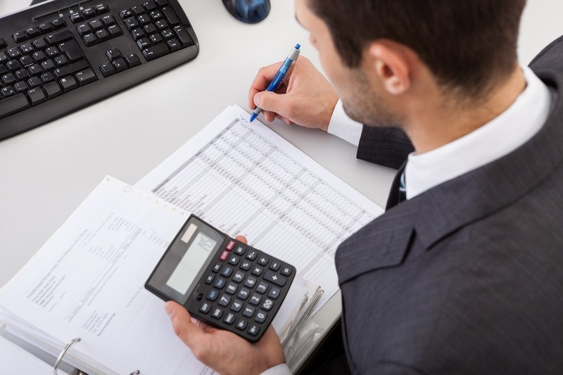 This photo shows an over the shoulder shot of a man in business clothes writing something on an accounting paper while his other hand holds a calculator, representing an accountant at work.