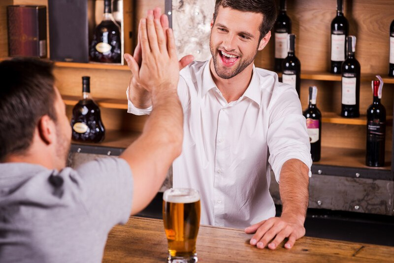 This photo shows the rear perspective of a man in a gray shirt sitting a bar, giving a high five to a smiling bartender in a white shirt, representing a bartender at work.