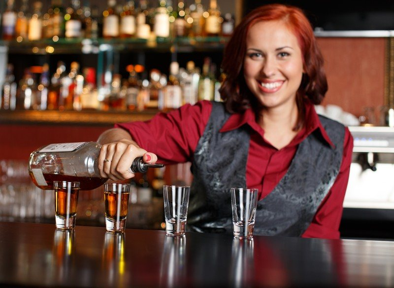 This photo shows a pretty readheaded bartender in a red blouse and gray vest pouring shots on a dark wooden bar.